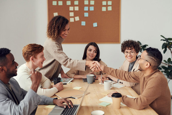 A group of businesspeople sit together at a table having a meeting. Two of them are shaking hands.